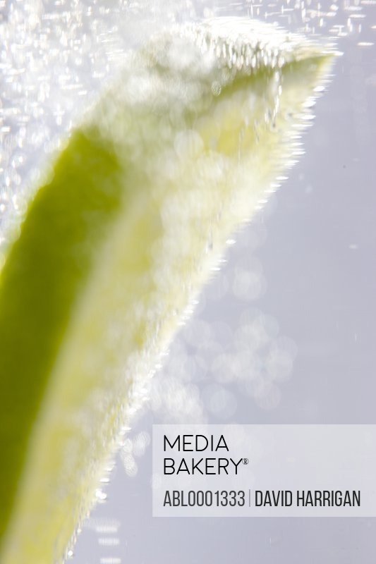 Extreme close up of a slice of lime floating in sparkling water