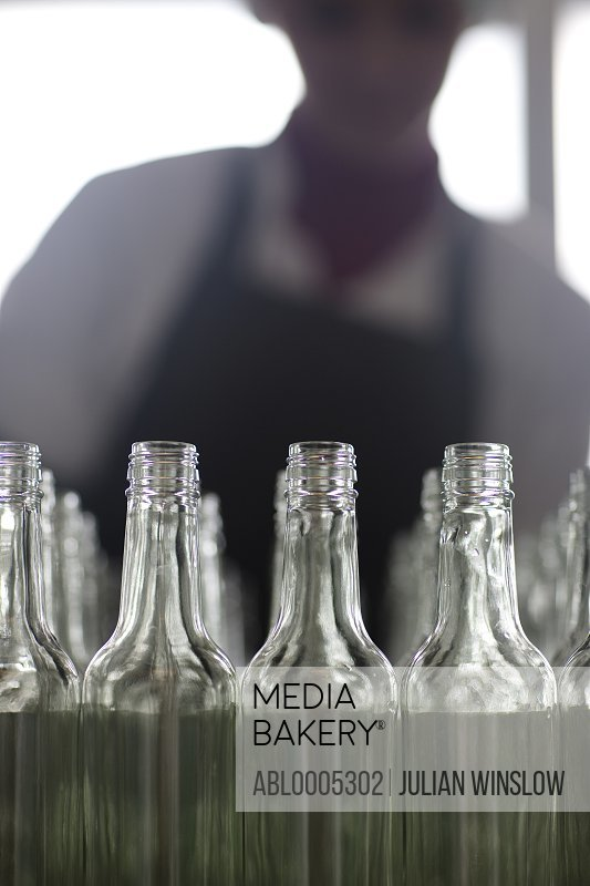 Lined up glass bottles and factory worker