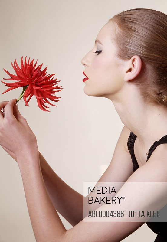 Portrait of young beautiful woman holding red dahlia