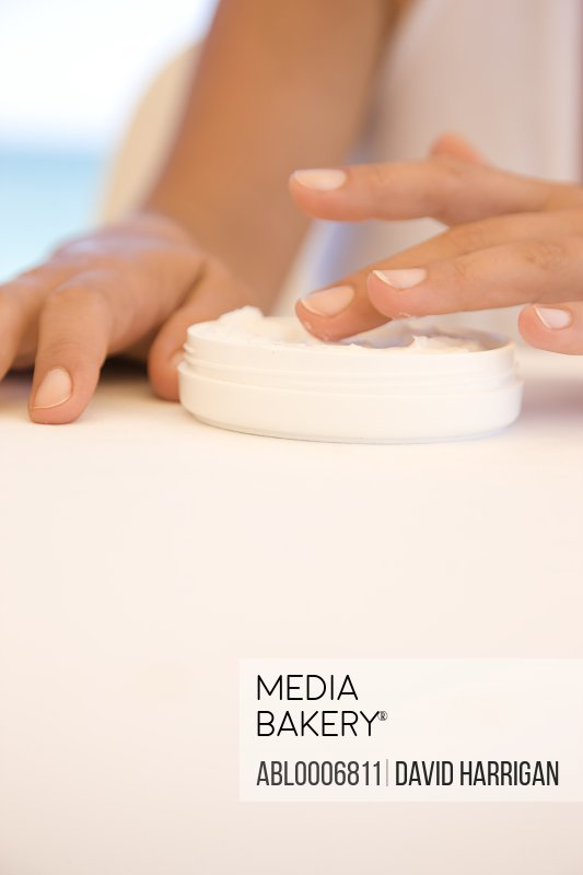 Woman's Hands Getting Cream out of Jar