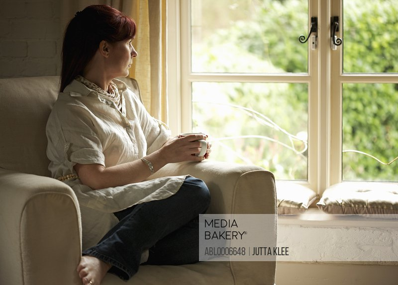 Woman Sitting on Armchair Holding Coffee Cup Looking out of Window