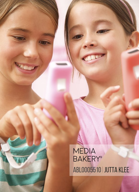 Two smiling girls inspecting a game controller