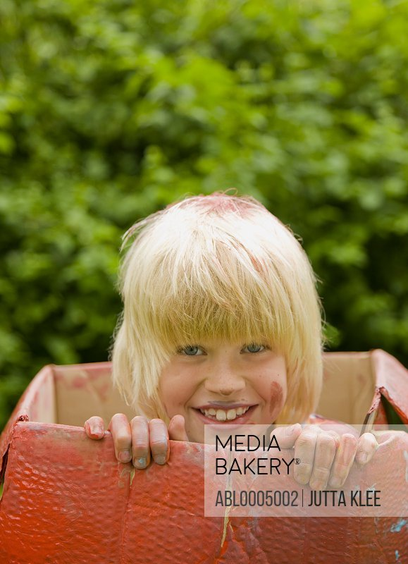 Close up of a young blonde boy in a cardboard box smiling