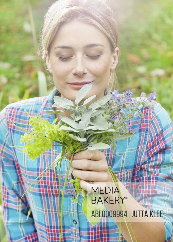Woman in Garden Smelling a Bunch of Herbs and Flowers