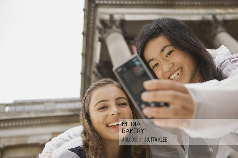 Two teenage girls taking self-portrait with cell phone in front of National Gallery