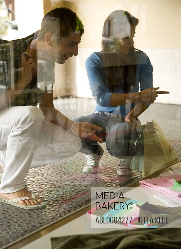 Portrait of young couple crouching and looking into shop window