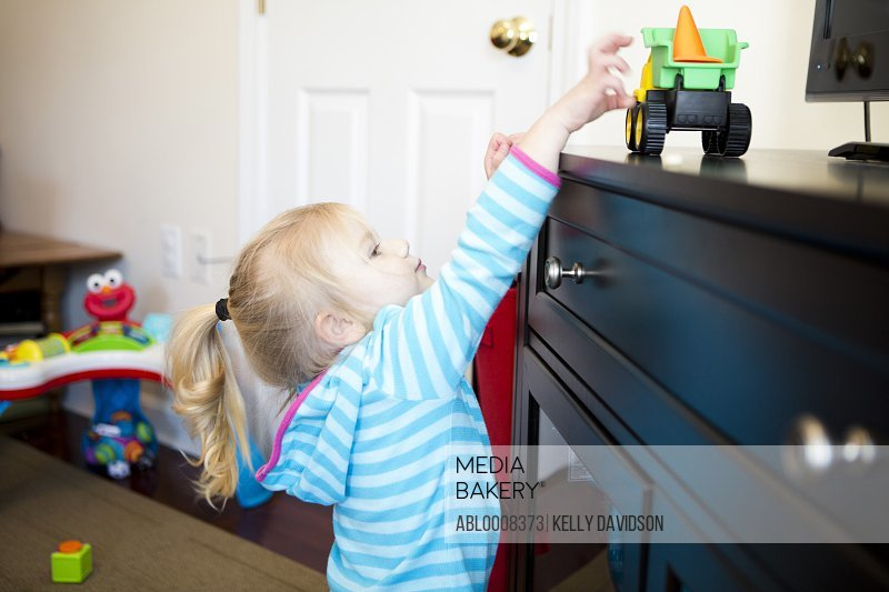 Girl Reaching for Toy
