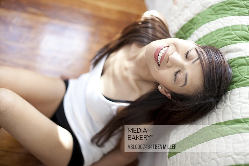 Woman Sitting on Floor Leaning against Bed
