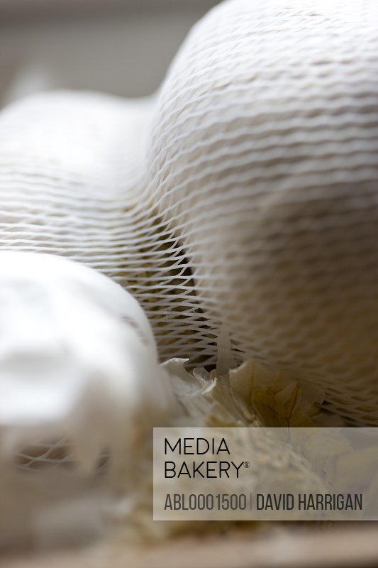 Close up of garlic bulbs in a mesh bag