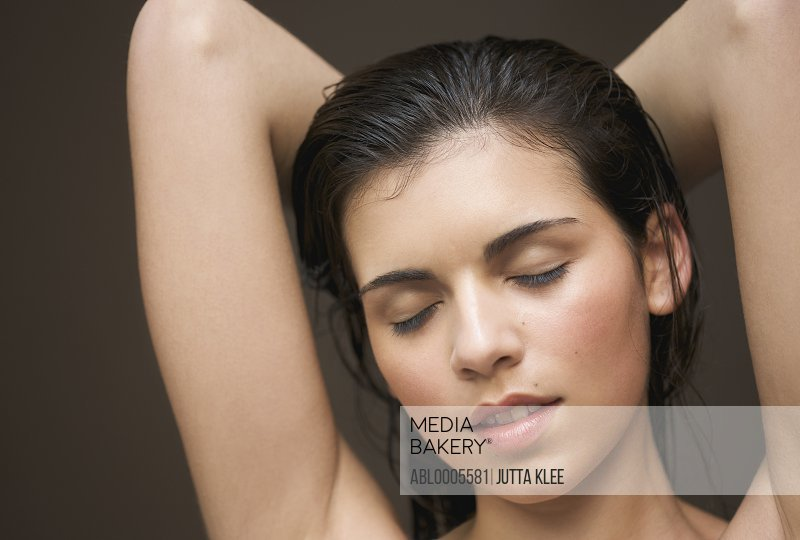 Woman with her arms crossed behind her head