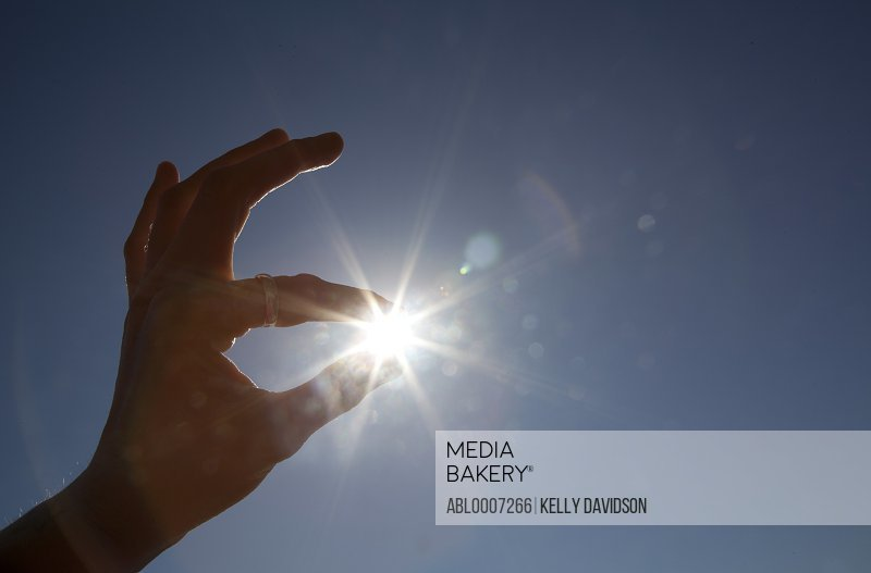 Man's Hand with Sun Between Fingertips