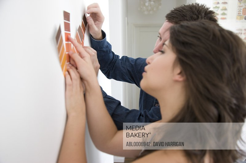 Couple Holding Colour Swatches against Wall