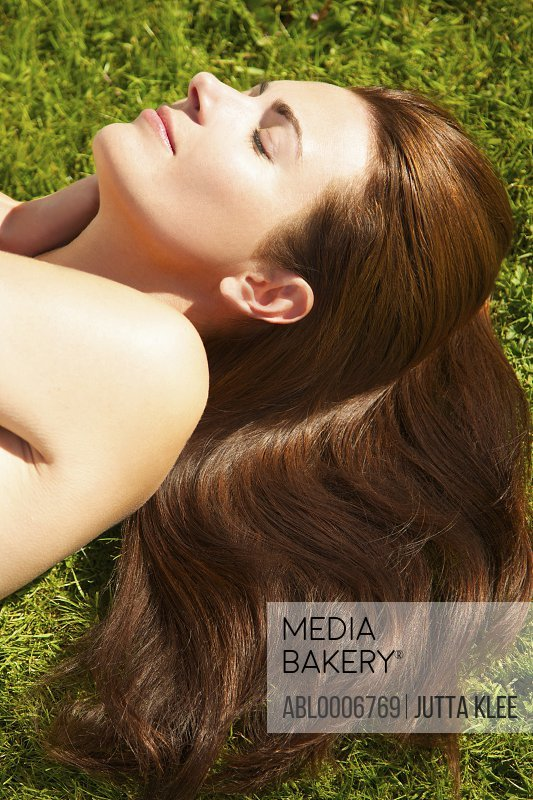 Woman with Long Wavy Hair Lying on Grass, Close-up view