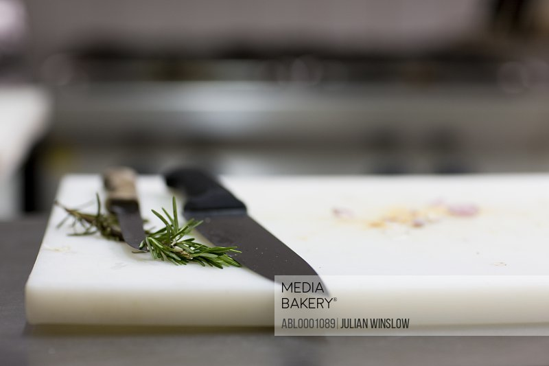 Close up of kitchen knives and a rosemary twig on a cutting board