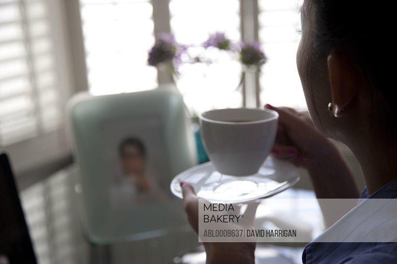 Woman Sitting at Desk Having Coffee