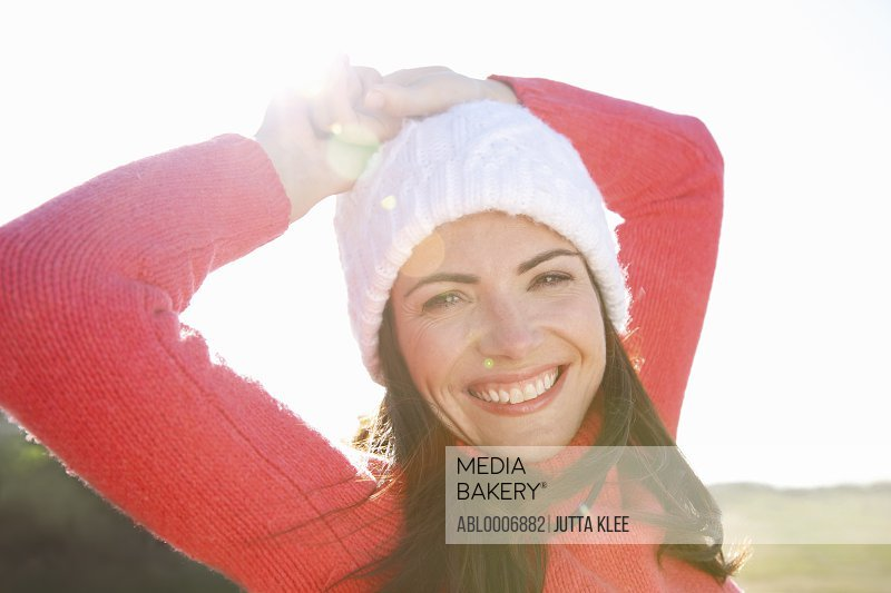 Smiling Woman with Hands on Head Wearing Wollen Hat