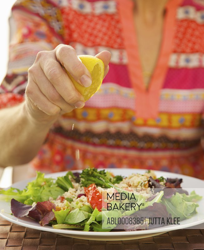 Woman's Hand Squeezing Lemon on Couscous Salad