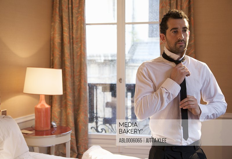 Businessman in hotel room tying his tie