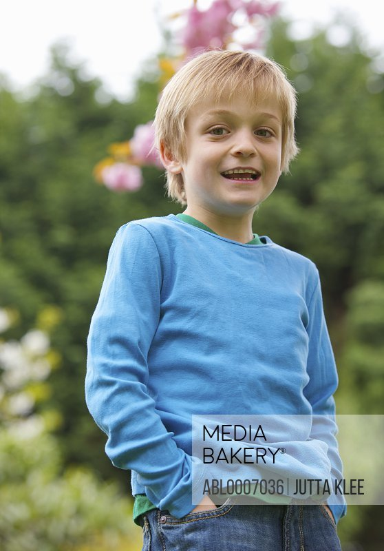 Boy Standing in a Garden with Hands in Pockets
