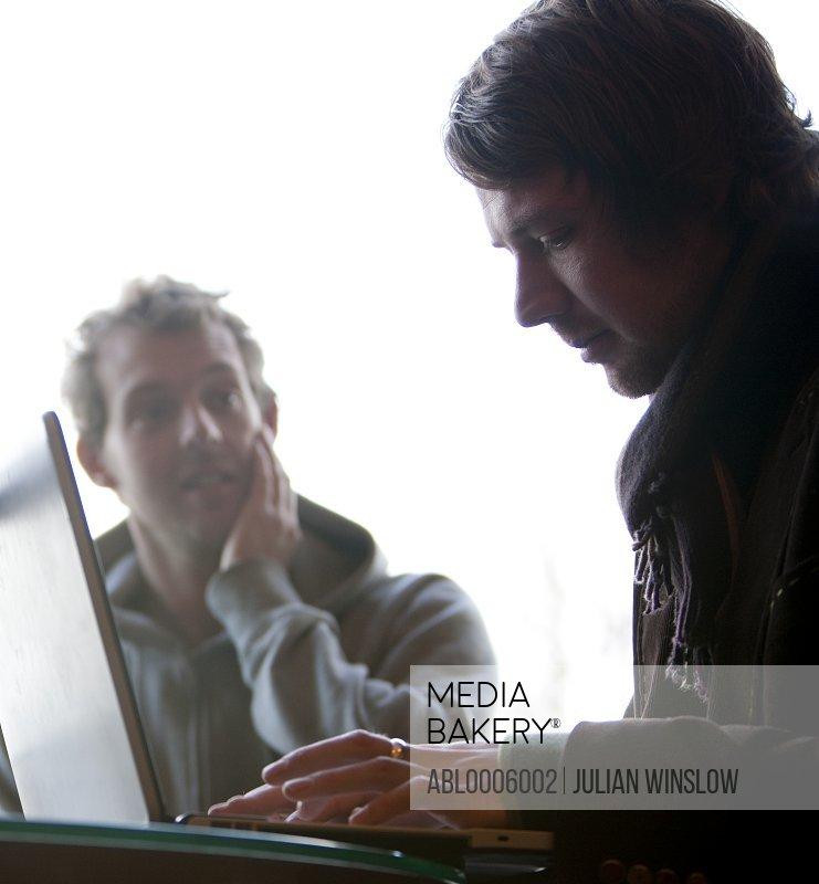 Two men using a laptop