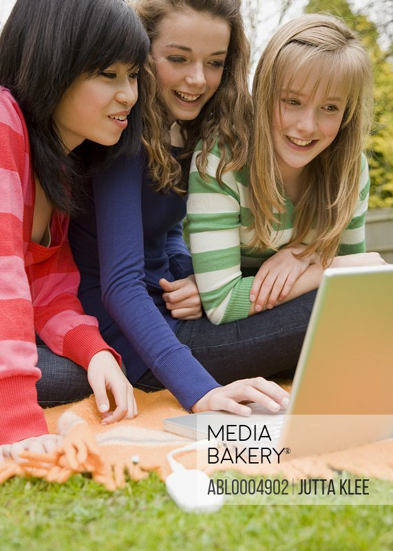 Teenage girls looking at laptop computer typing and smiling