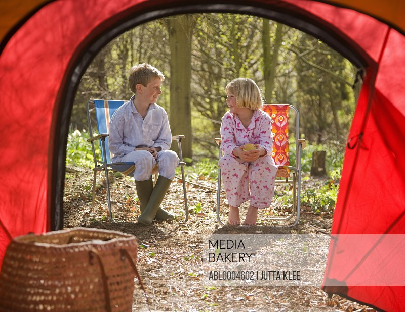 Portrait of boy and girl sitting outside tent entrance