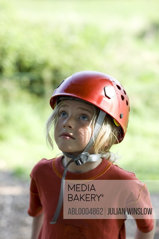 Young girl wearing a protective helmet looking up