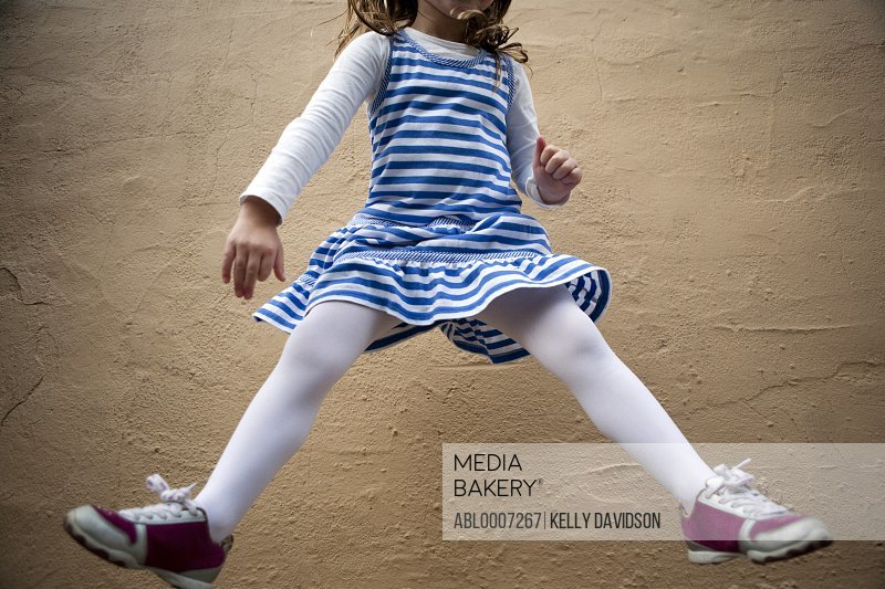 Girl Jumping Mid Air in front of Wall, Cropped