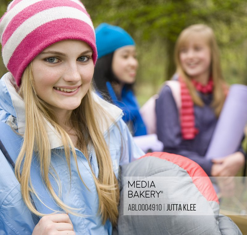 Smiling teenaged girl wearing woolly hat with friends carrying camping equipment