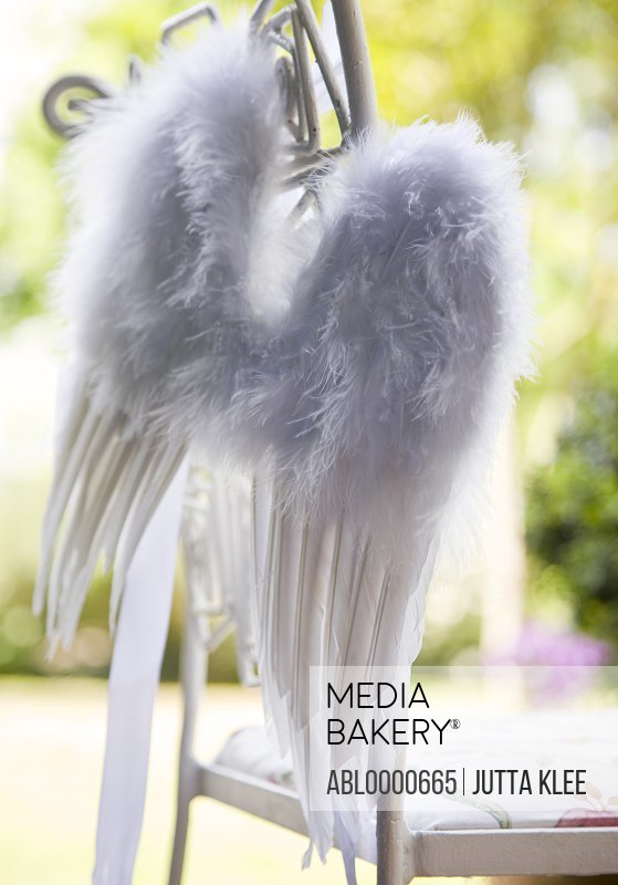 Close up of white feather wings hanging from  garden chair