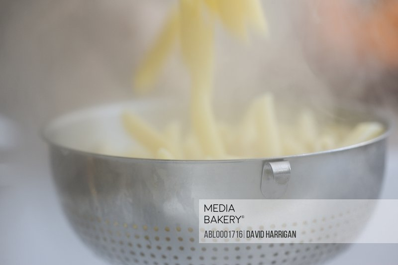 Draining penne pasta into a colander
