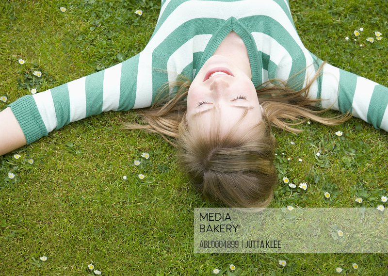 Teenaged girl lying on back with arms wide open relaxing and smiling