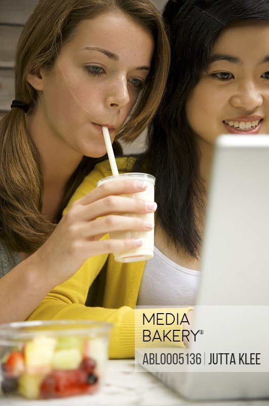Two teenaged girls sitting in front of laptop computer typing and drinking milk-shake