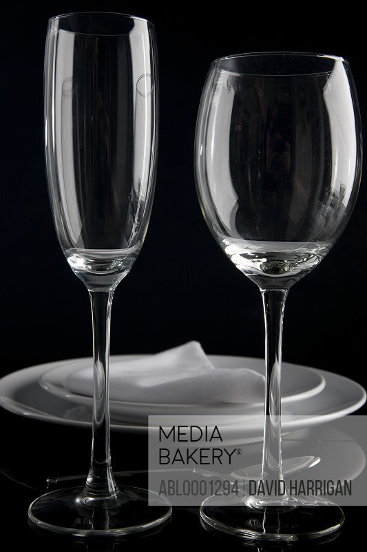 Close up of a place setting with plates napkin and two wine glasses