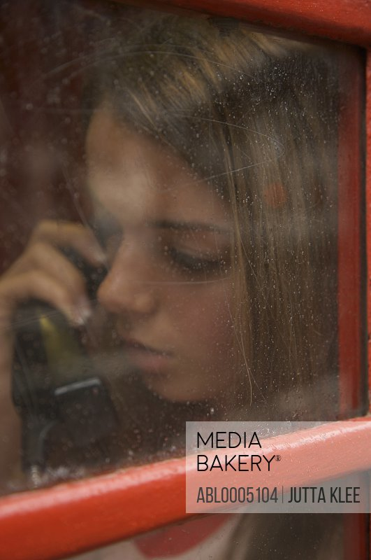 Teenaged girl talking on the telephone inside a London phone booth