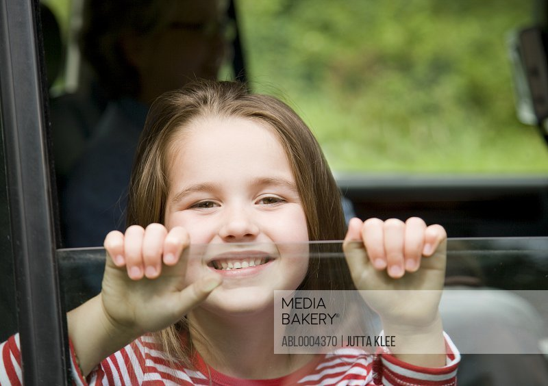 Young girl smiling with hands holding car window