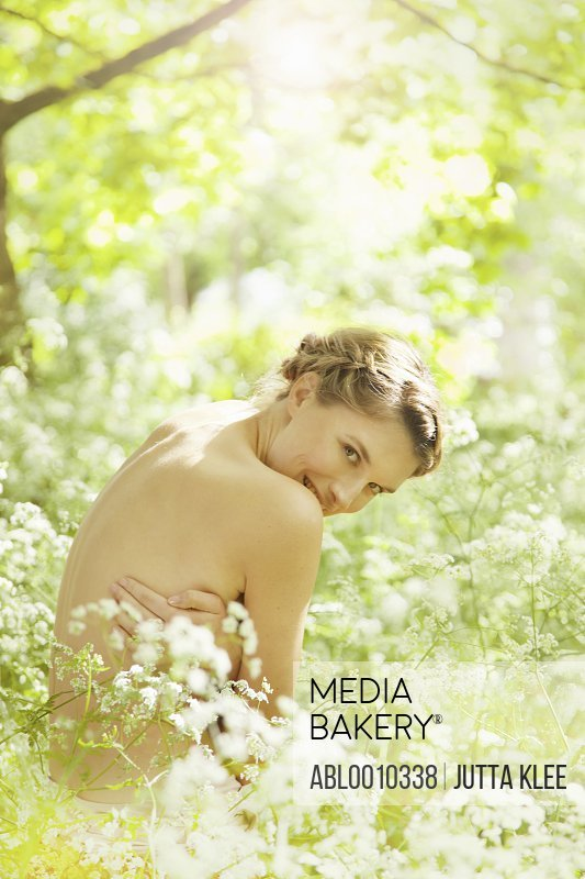 Nude Woman Hugging herself in a Meadow Smiling