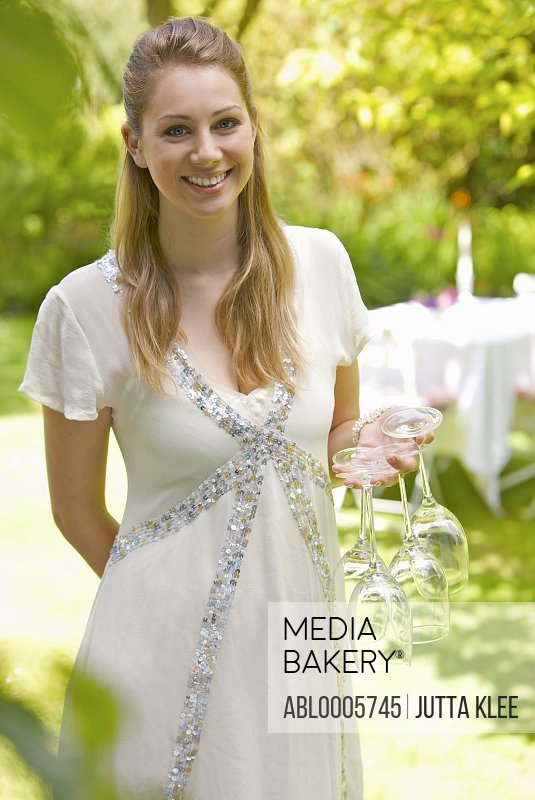 Smiling young woman standing in a garden holding wine glasses