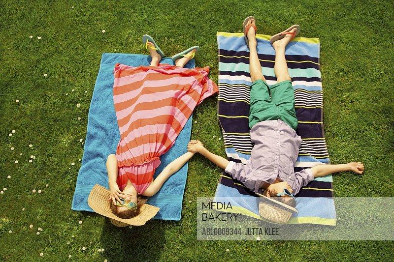 Boy and Girl Sunbathing on Lawn