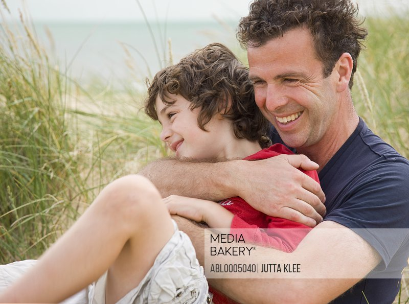 Father and son sitting on a beach smiling and embracing