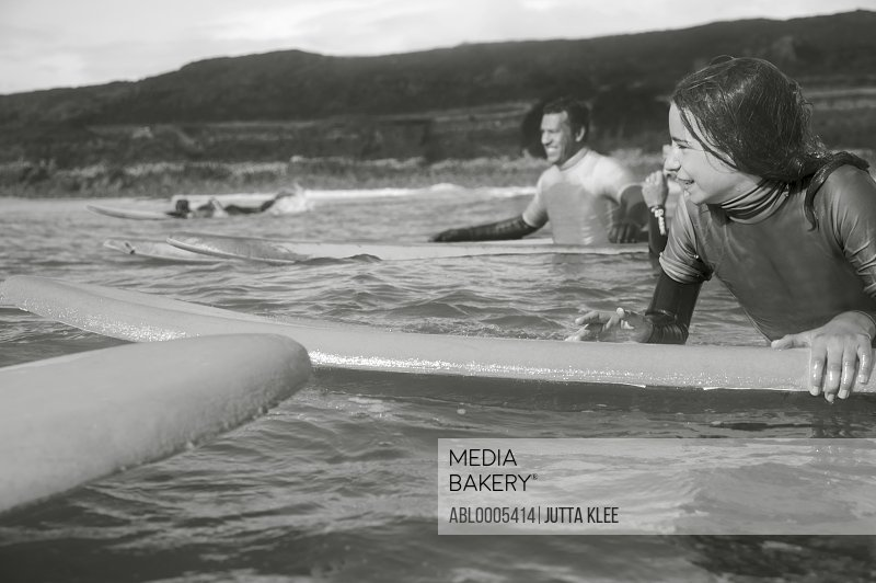 Girl in the sea holding on to her surfboard with surfer behind her