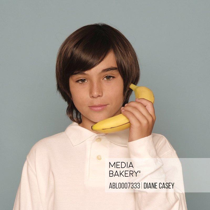 Boy Holding Banana as if Telephone