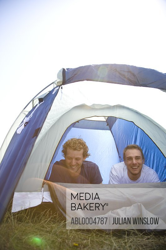 Two young campers lying on stomach inside tent laughing
