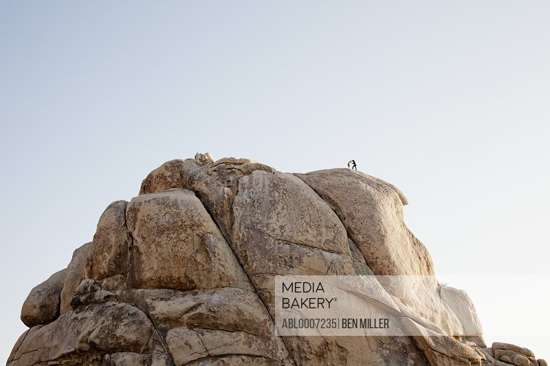 Rock Climbers Preparing to Abseil Boulder