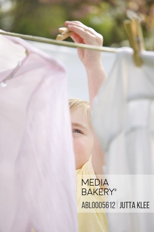 Close up of boy hanging clothes on a clothesline