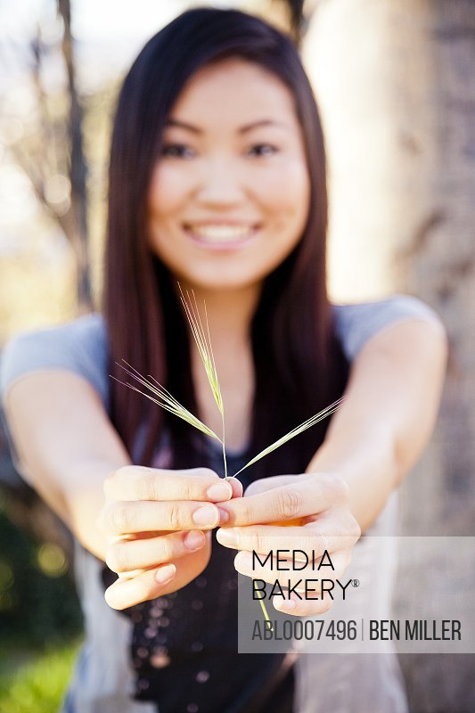 Smiling Young Woman Holding a Piece of Grass