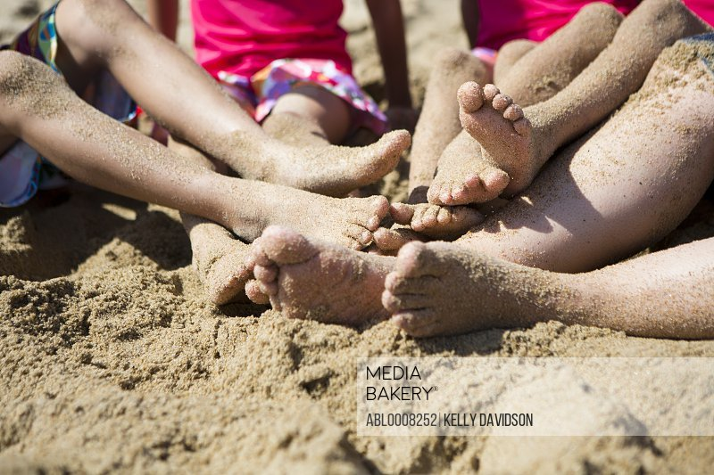 Sand Covered Legs and Feet of Woman and Four Children