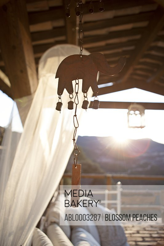Elephant Shape Wind Chime Hanging from Beamed Ceiling Veranda