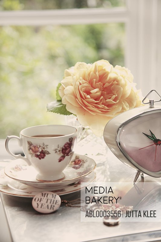 Teacup, Clock, Jewellery and Flowers on Woman's Dressing Table