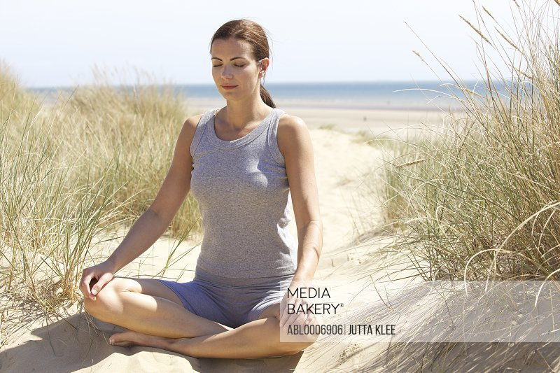 Woman Practicing Yoga on Sand Dune by Ocean